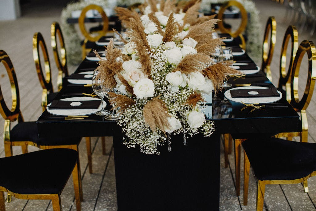 Black Modern Tablescapes with Mirrored Gold Accents and Wedding Centerpieces Featuring Garland of Baby's Breath, Pampas Grass, and White Roses   PartySlate