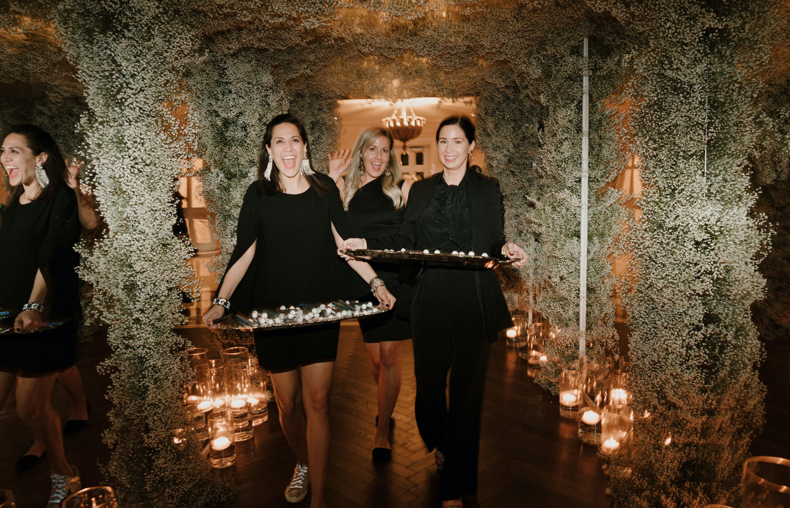 Three Wedding Staff Servers Smile Underneath Wedding Canopy Covered in Baby's Breath