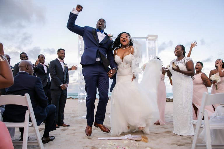 Bride and Groom Celebrate on Sandy Aisle After Oceanfront Exchange of Vows at The Palms Hotel & Spa | PartySlate