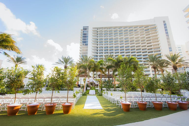 Outdoor Lawn Wedding Ceremony with Eden Roc Miami Beach in Background | PartySlate
