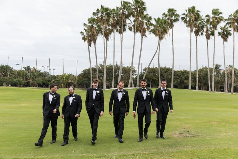 Groom's Party Poses in Front of Green Sprawling Lawn with Palm Trees in Backdrop | PartySlate
