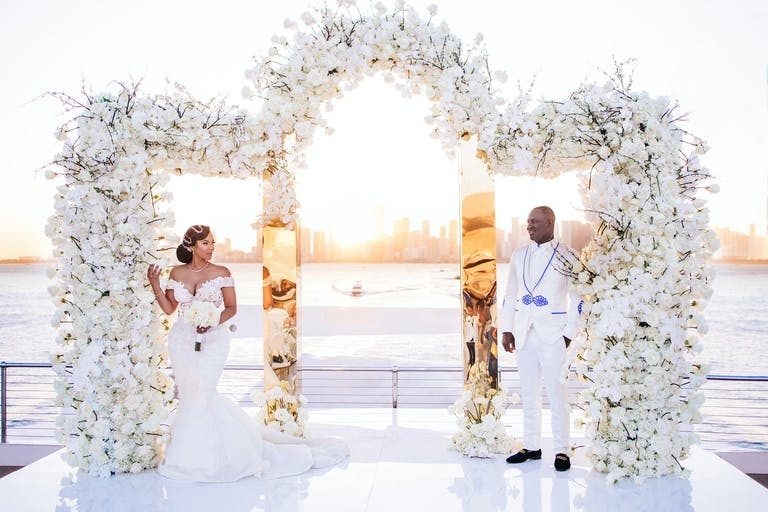 Bride and Groom Pose in Front of a Mirrored Trifold Gold Arch Covered in White Flowers | PartySlate