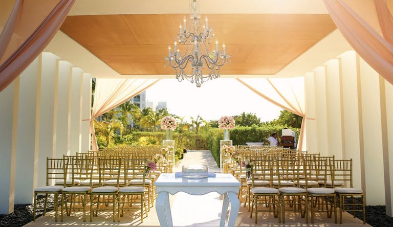 Covered Outdoor Wedding Ceremony With Pink and White Drapery and Chandelier | PartySlate