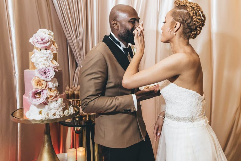 Bride Feeds Groom a Slice of Custom-Designed Pink Cake With Florals | PartySlate
