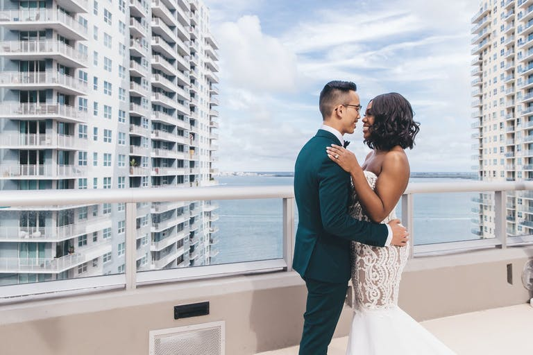 Wedding Photo of Bride and Groom on Balcony Overlooking Skyscraper and Ocean Captured by Stanlo Photography | PartySlate