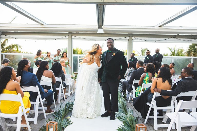 Bride and Groom Pose During Recessional Down Aisle | PartySlate