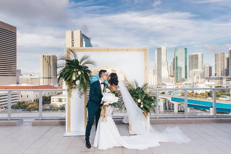 Bride and Groom Kiss In front of Modern Arch at PENTHOUSE at Riverside Wharf Overlooking Skyline | PartySlate
