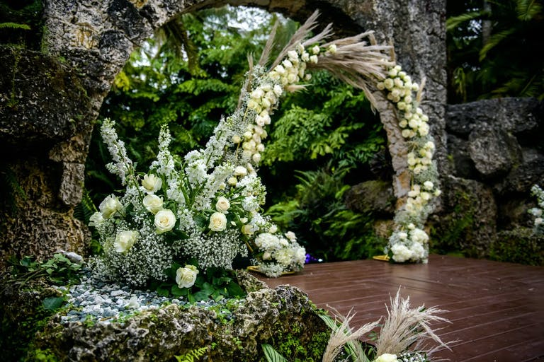 White Circular Wedding Arch With Lush Greenery | PartySlate