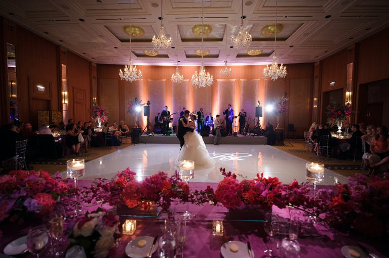 Bride and Groom Dance on White Dance Floor Behind Pink-Floral Tablescapes at Ballroom in The Peninsula Chicago   PartySlate