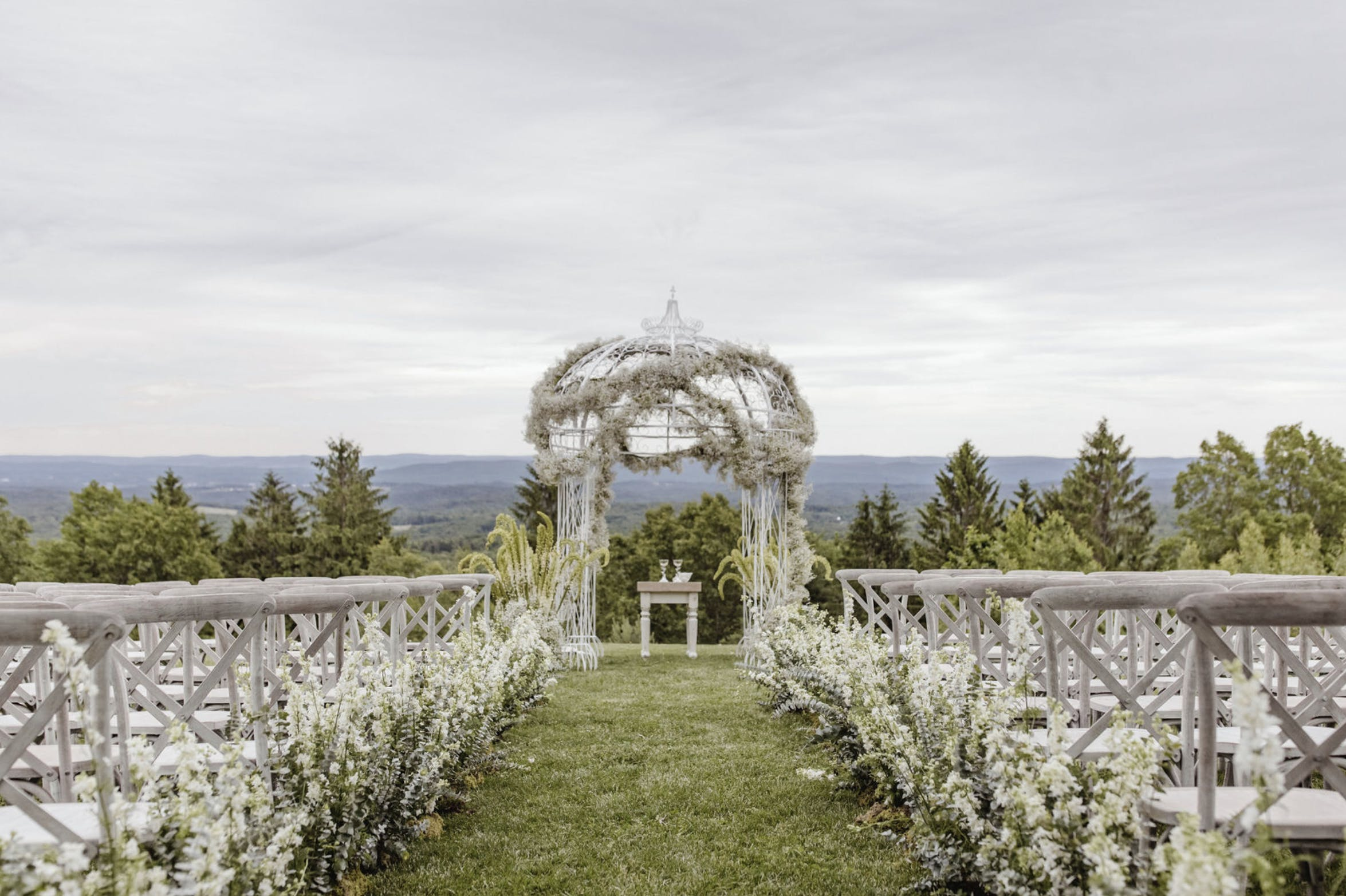 A White Filigree Wedding Arbor Wound with a Garland of Baby's Breath   PartySlate