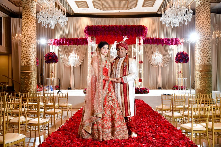 Bride and Groom Stand in Front of Rose-Covered Mandap at South Asian Wedding at Hilton Chicago   PartySlate