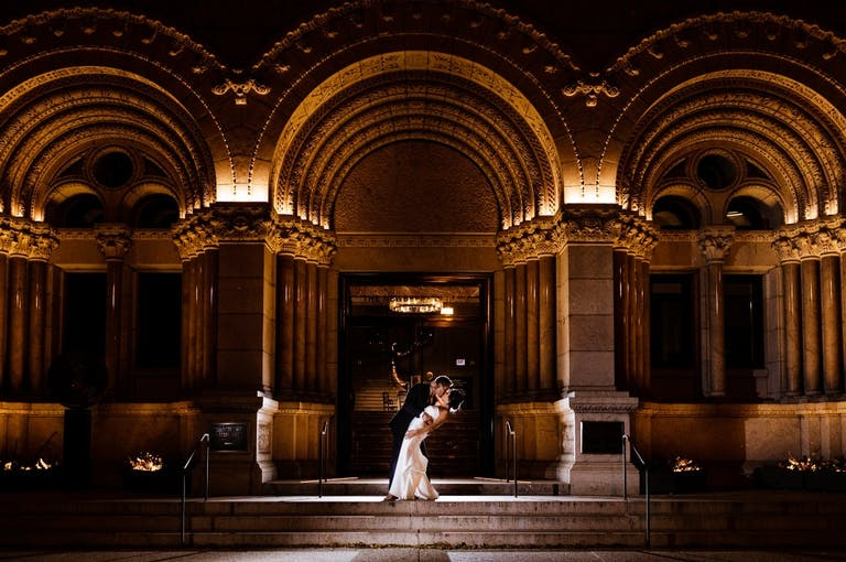 Couple Kiss in Front of Dramatic Curved Arches of The Newberry Library, a Unique Chicago Wedding Venue