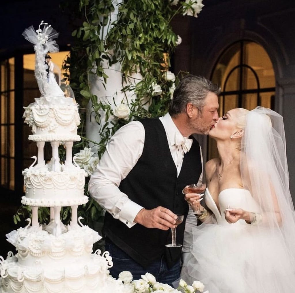 Gwen Stefani and Blake Shelton Kiss in front of Tiered White Wedding Cake | PartySlate