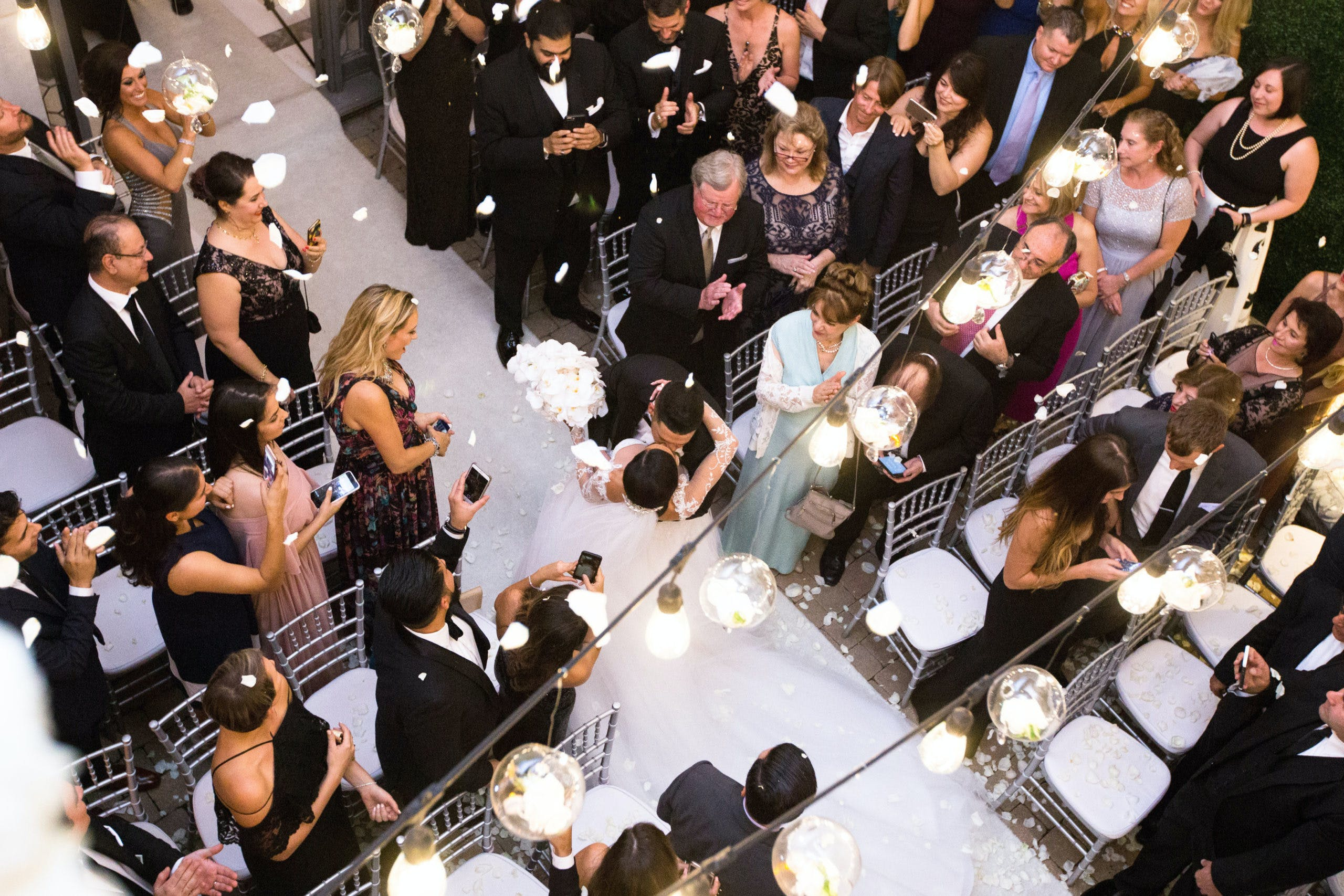 Aerial view of a wedding reception and bride and groom kissing in middle of aisle   PartySlate
