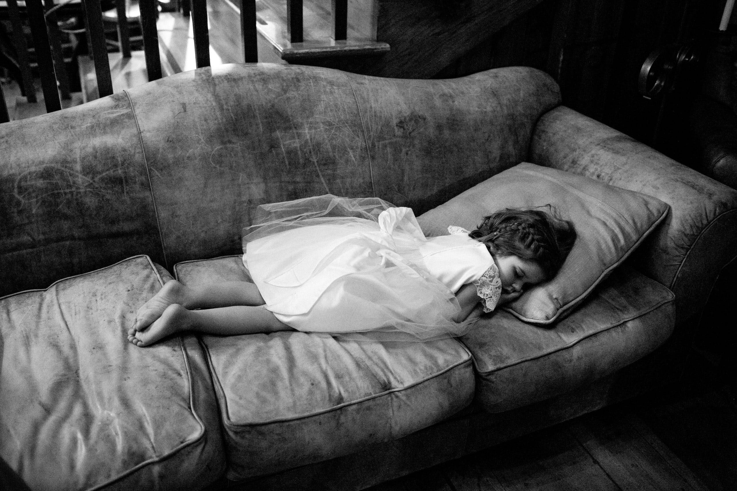 Flower girl peacefully sleeping on couch   PartySlate
