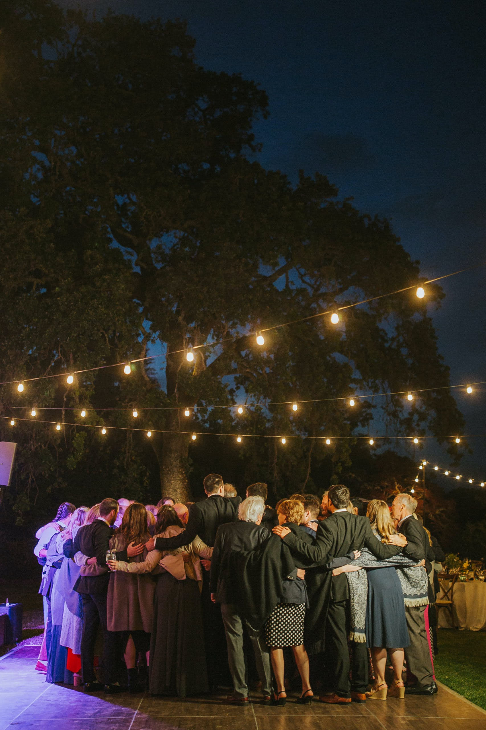 Group hug on dance floor at night with string lights décor   PartySlate