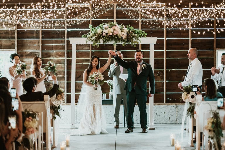 Newlywed couple at floral alter under twinkling lights at Heritage Prairie Farm in Elburn, IL | PartySlate