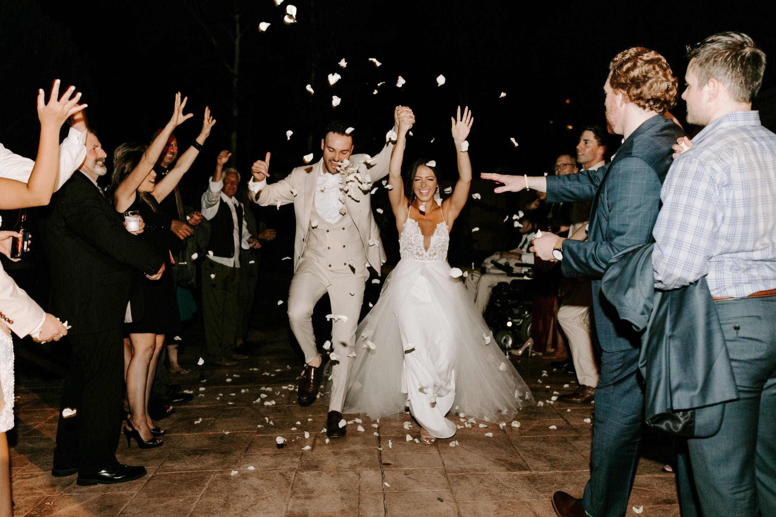 Guest throwing confetti at bride groom during reception   PartySlate