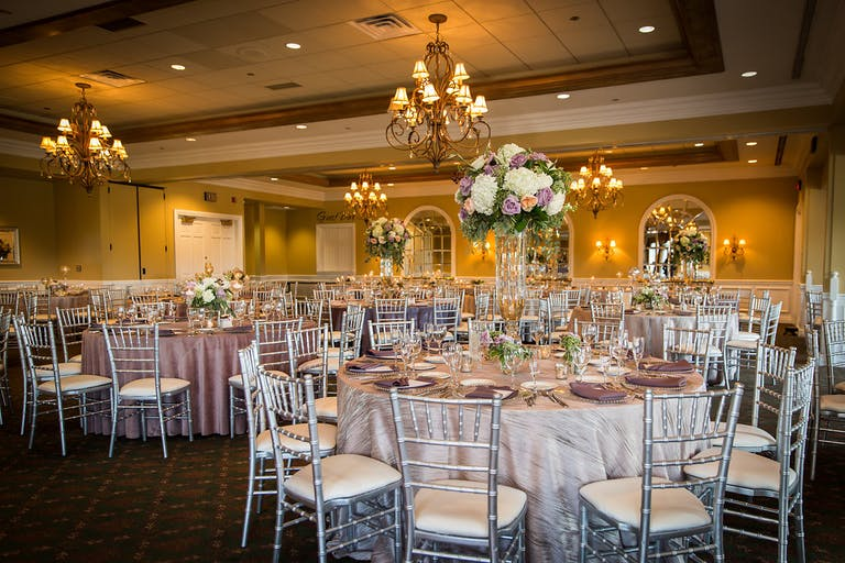 Reception room filled with tables with purple floral centerpieces and stunning gold chandeliers at White Eagle Golf Club in Naperville, IL | PartySlate