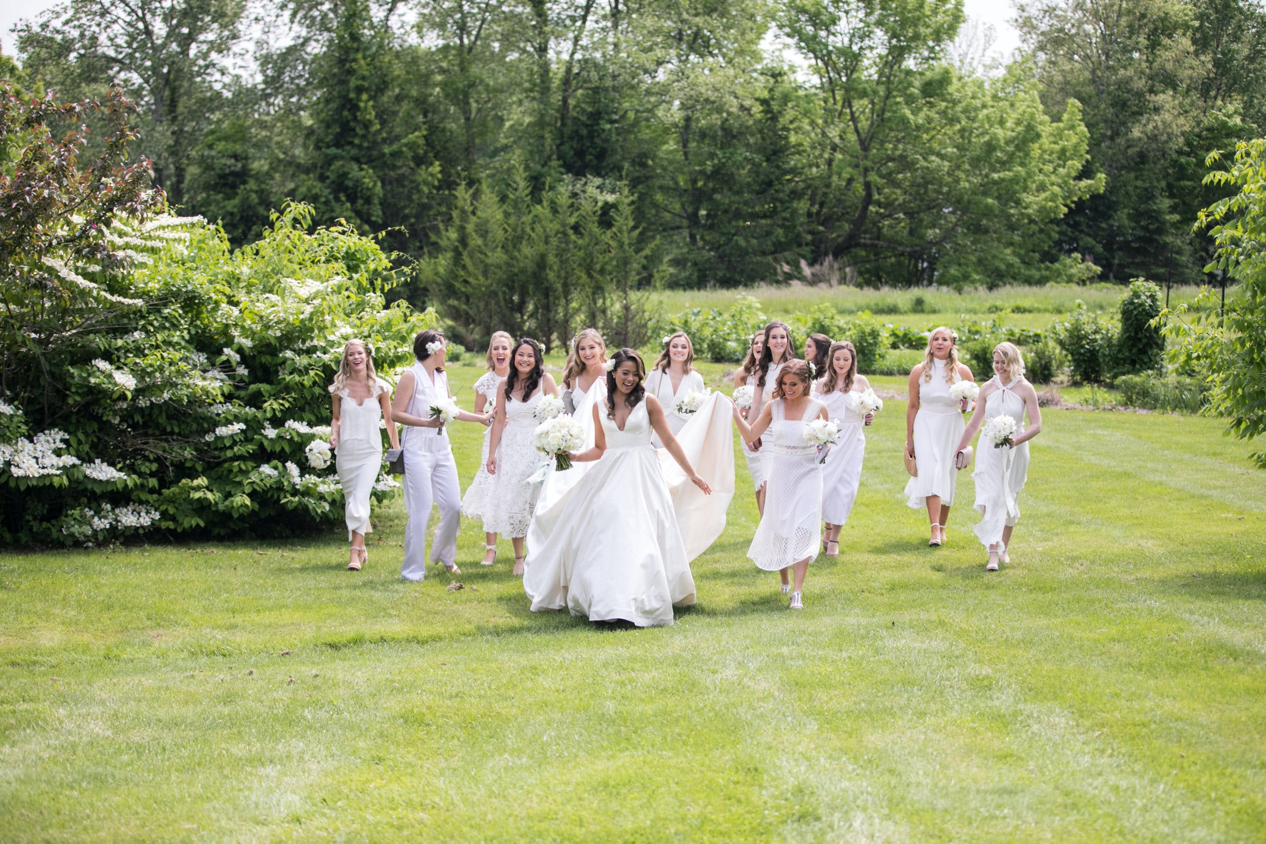 Bridal party in all white running through greenery field   PartySlate