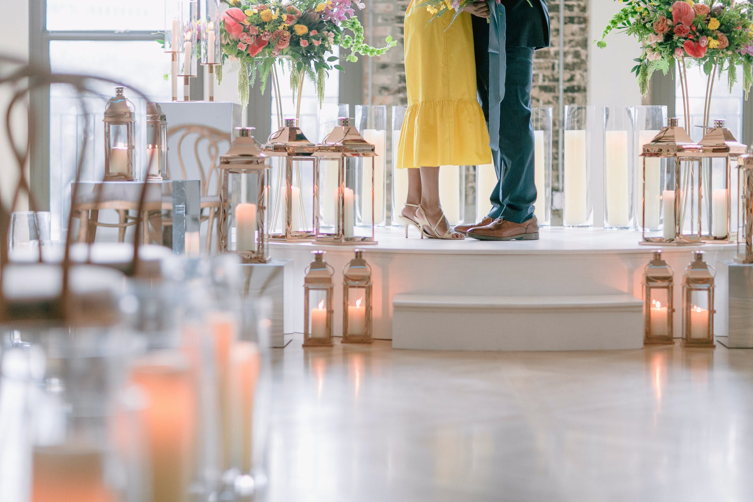 feet shot of aisle lit with lanterns and bride in yellow dress l PartySlate