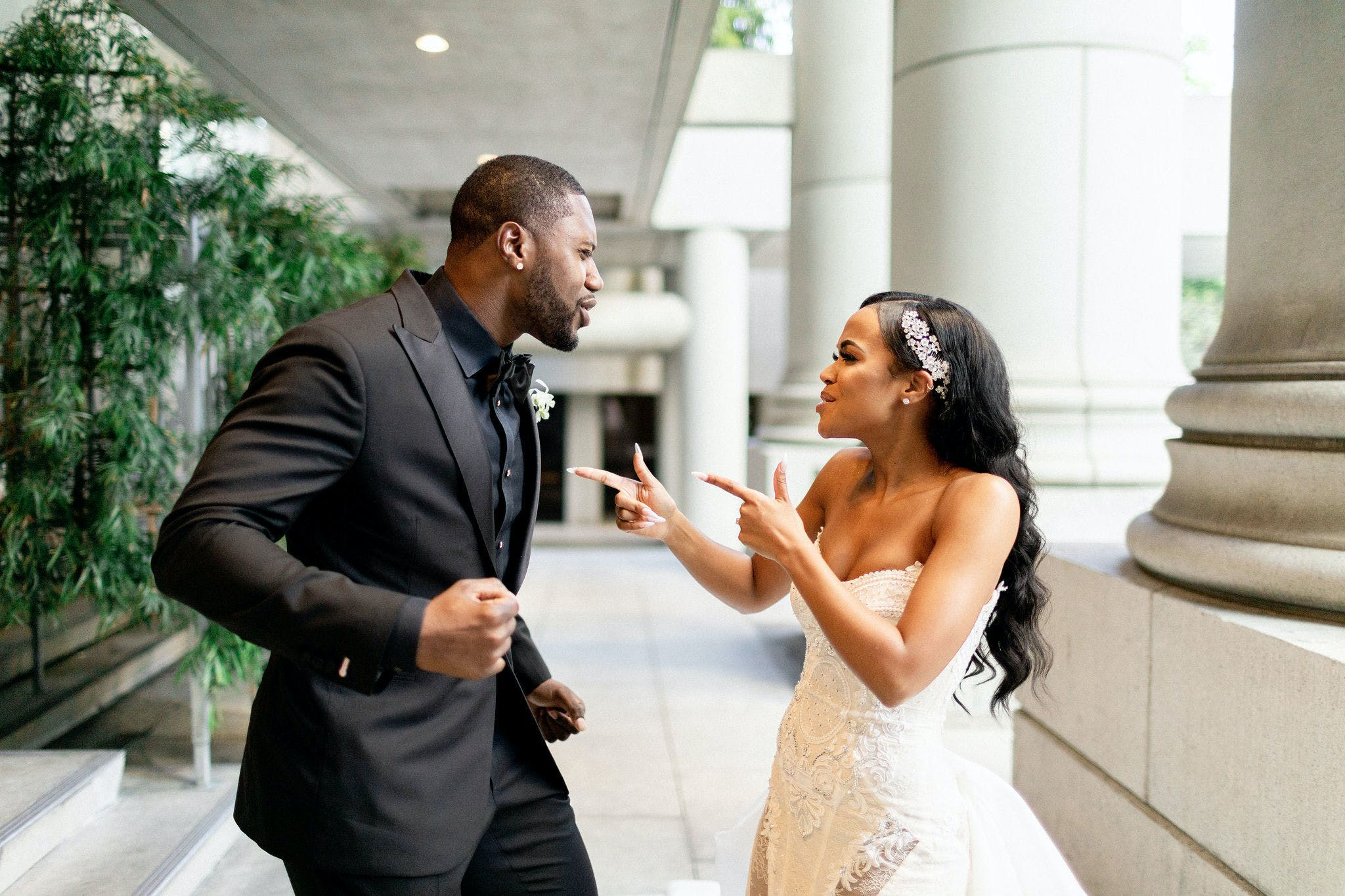 Bride and groom having a silly moment, bride doing finger guns at groom in all black suit   PartySlate
