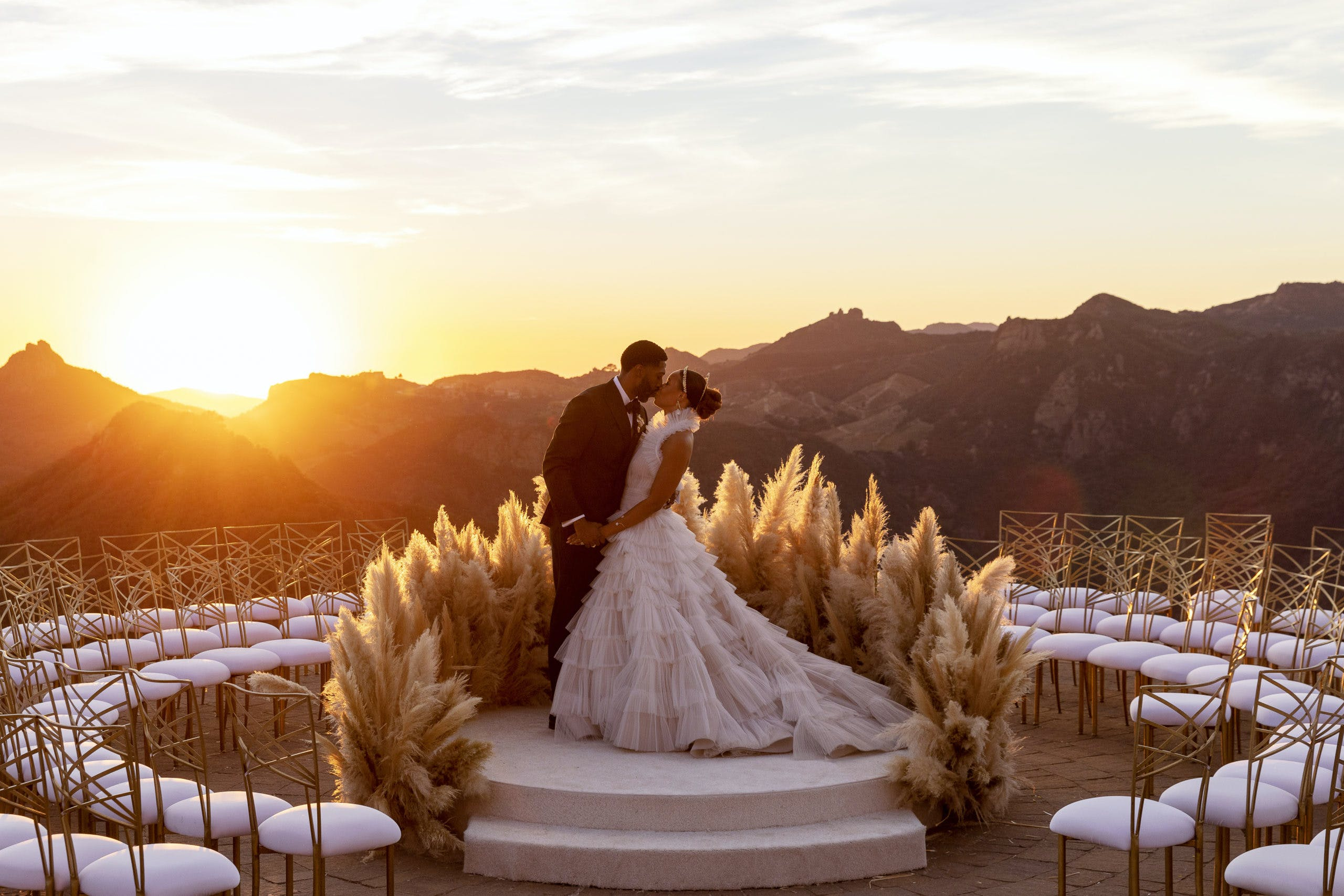 Bride and groom kissing with mountain background and sun setting   PartySlate