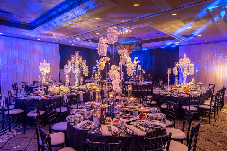 Blue uplit wedding reception with orchid décor at Concorde Banquets in Kildeer, IL | PartySlate