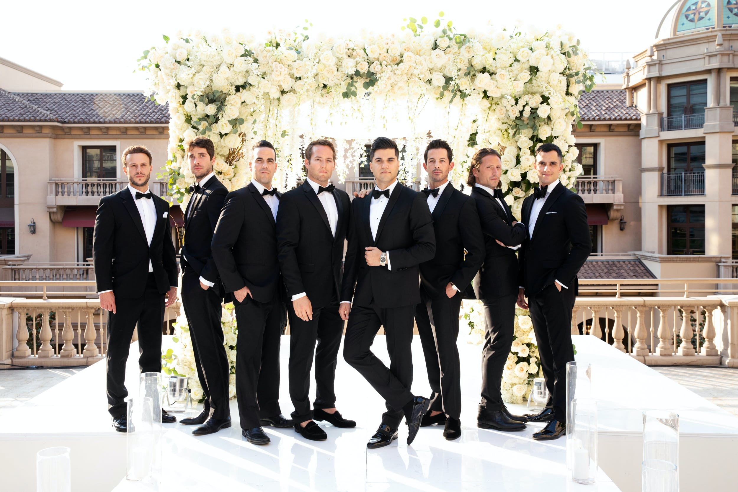 8 groomsmen in black tuxedos striking a pose in front of wedding arch   PartySlate