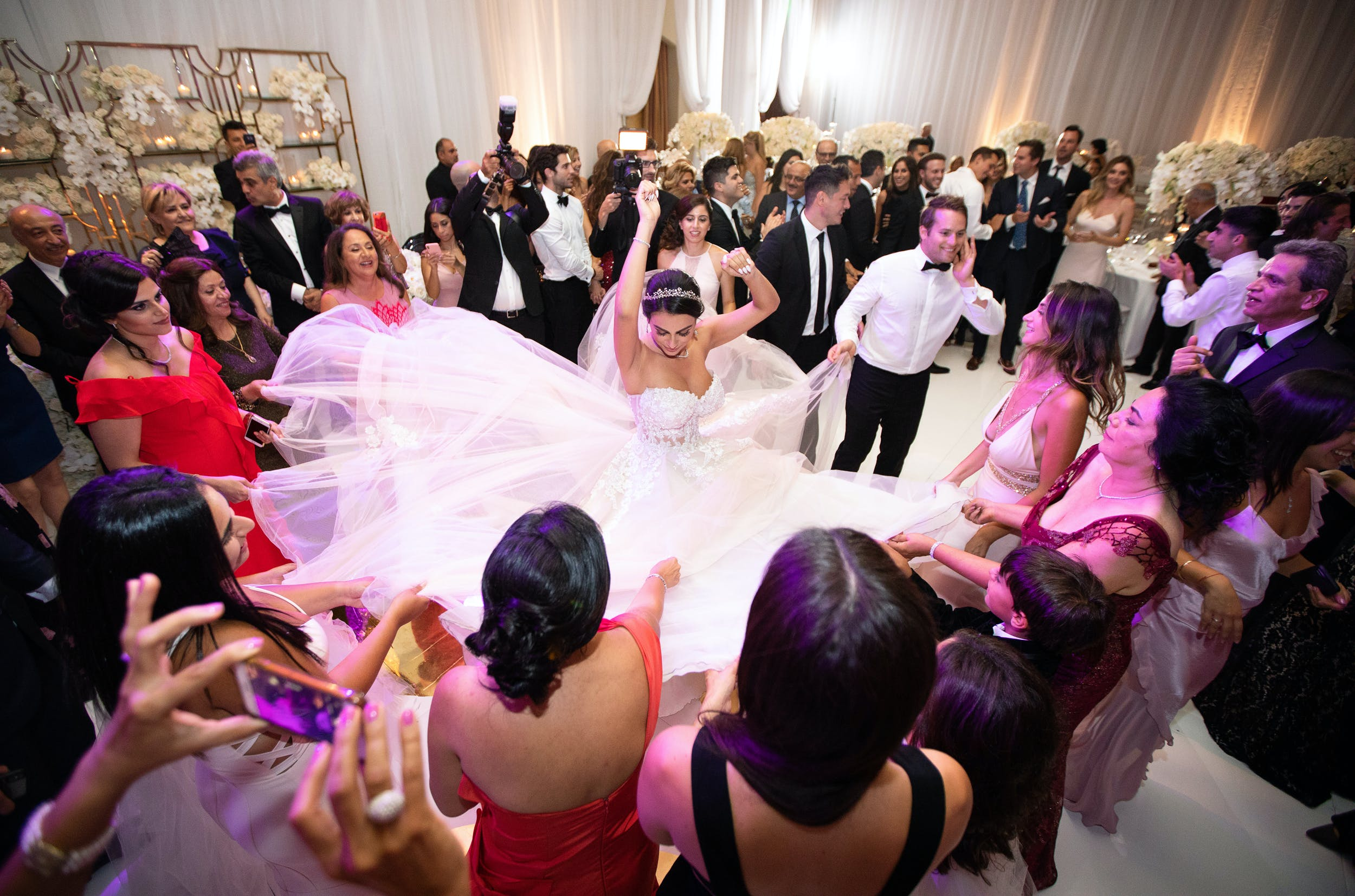 Bride twirling to showcase her dress on dance floor surrounded by wedding guests   PartySlate