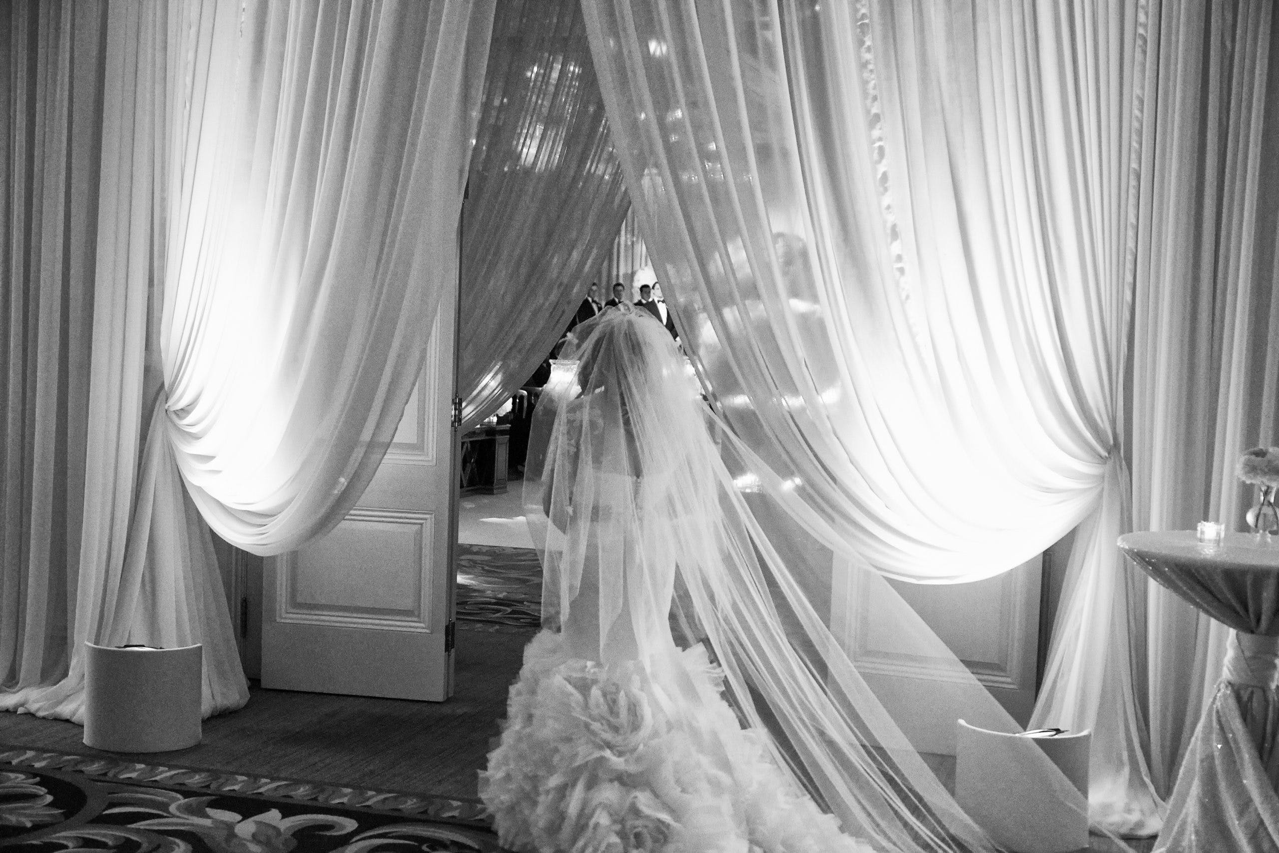 Black and white photo of bride looking into ballroom   PartySlate