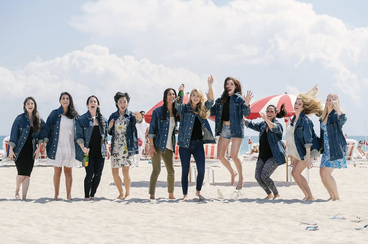 Bridal party jumping on the beach in matching jean jackets