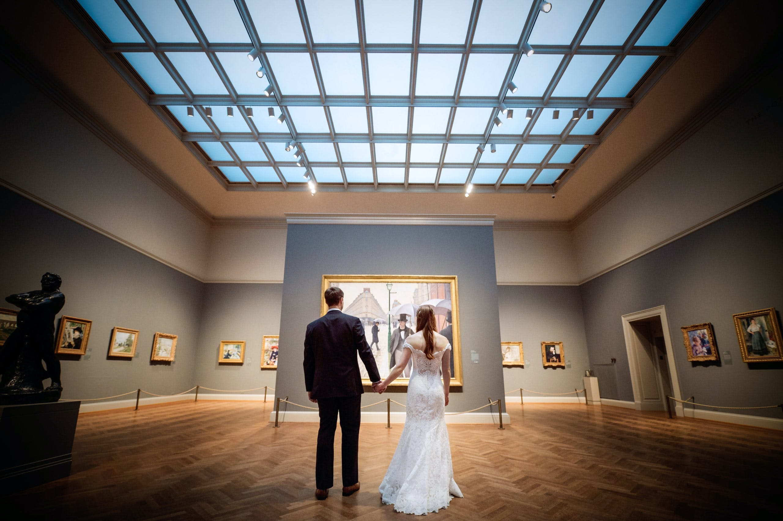 Shot of bride and groom from behind looking at art in museum   PartySlate
