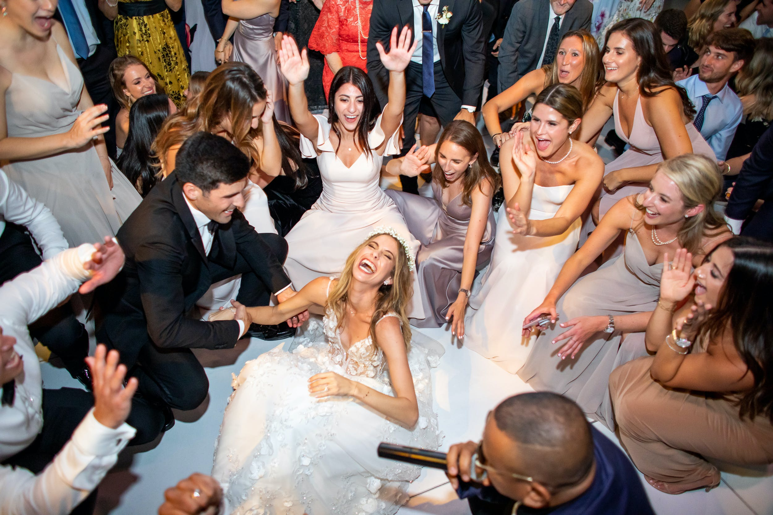 Bride, groom and friends dancing and laughing on dance floor during wedding reception   PartySlate