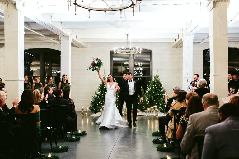 Happy couple at the altar rejoicing at elegant loft wedding with string-lit evergreen trees in backdrop at Company 251 in Aurora, IL | PartySlate