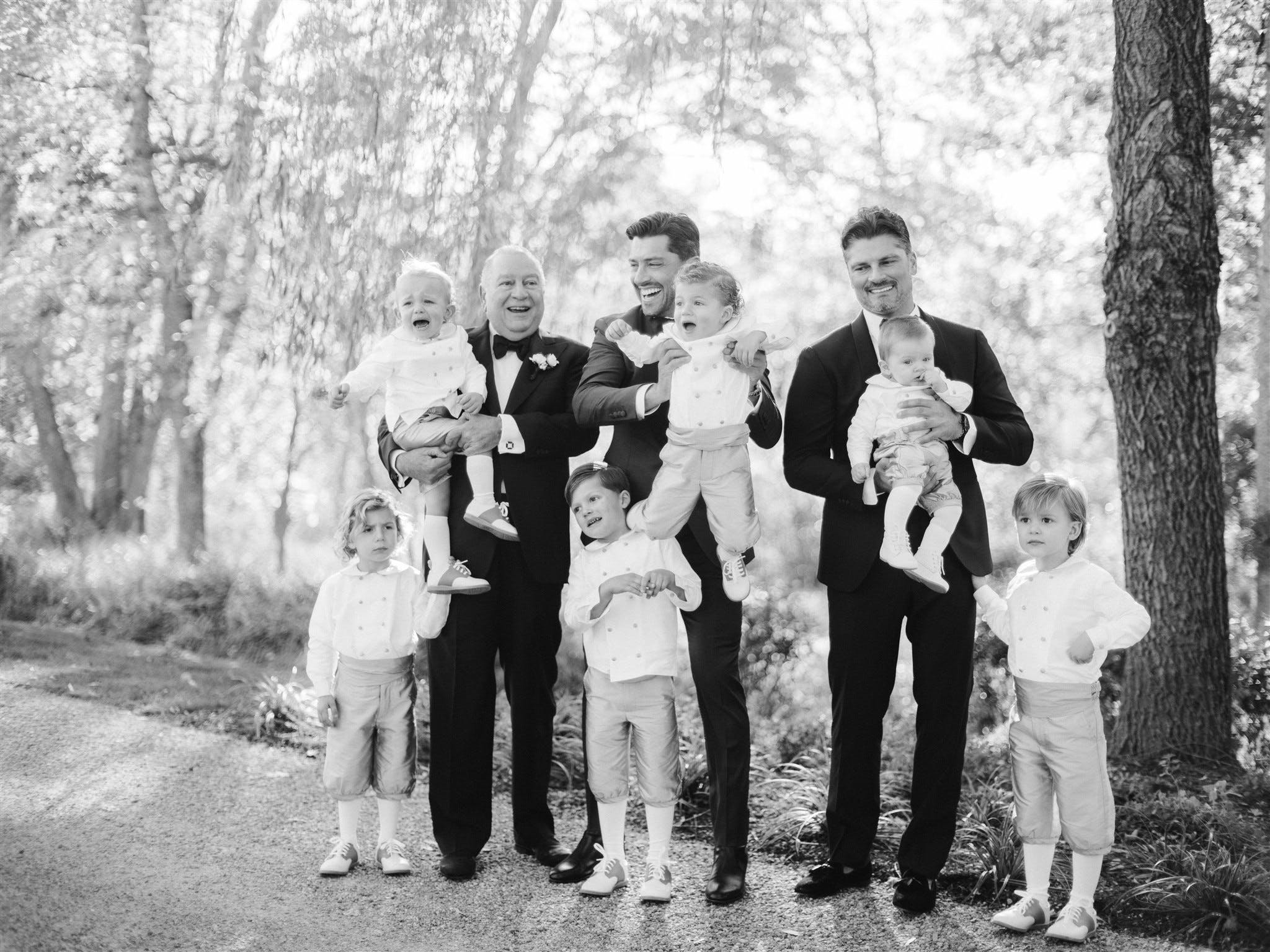 Black and white photo of six kids and three men all smiling and matching   PartySlate