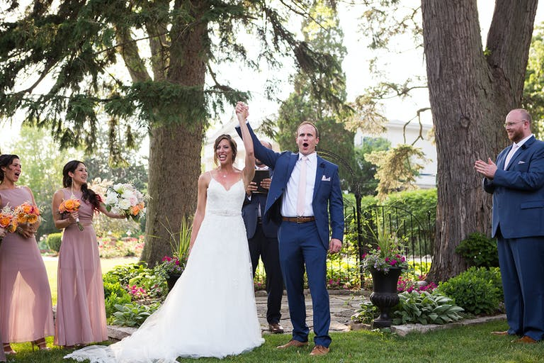 Bride and groom celebrate after exchange of vows at outdoor ceremony at Mesón Sebika in Naperville, IL | PartySlate