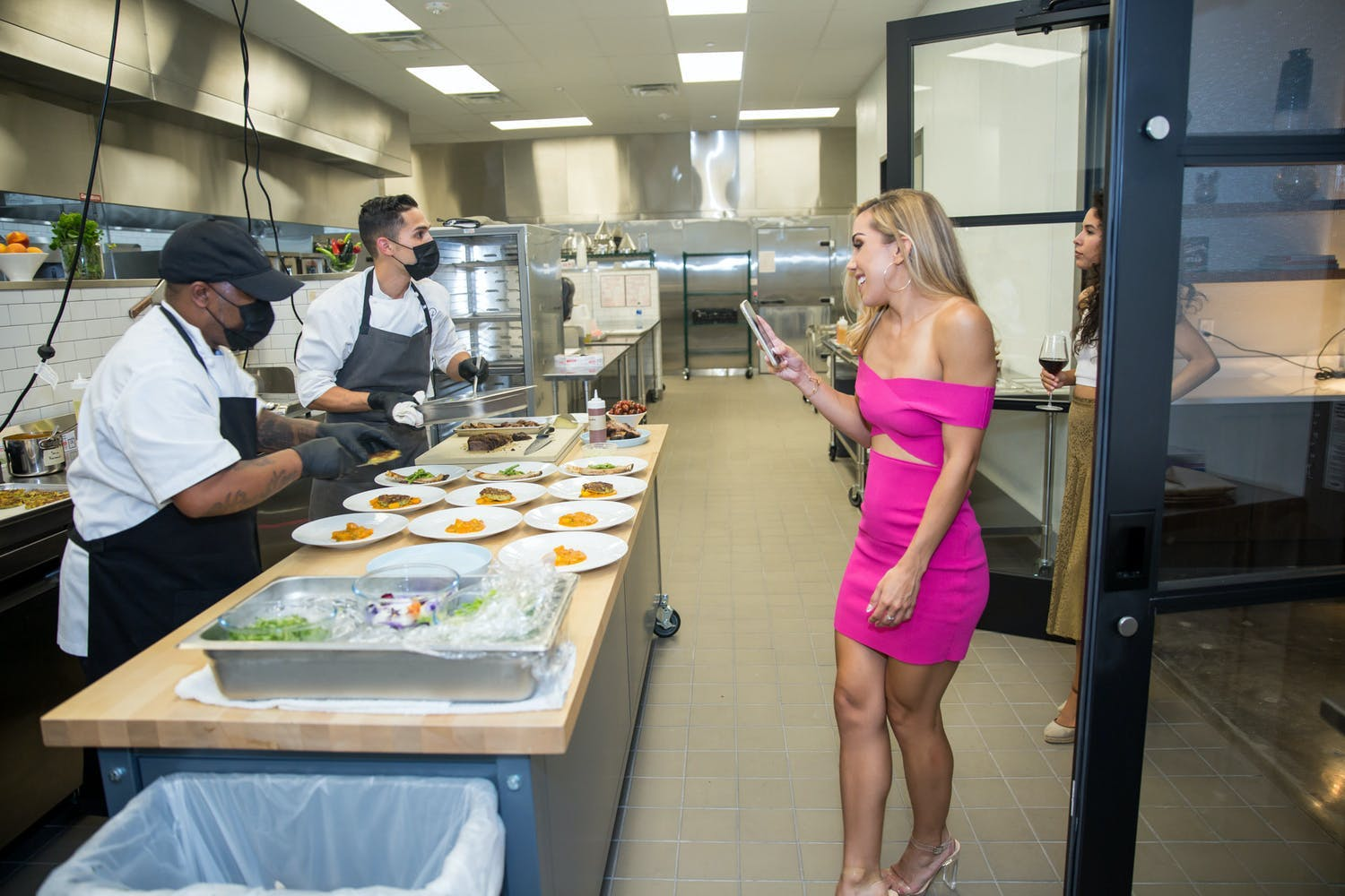Woman in Pink Dress Takes a Photo on her Phone of Chef's Preparing Meal in Kitchen | PartySlate