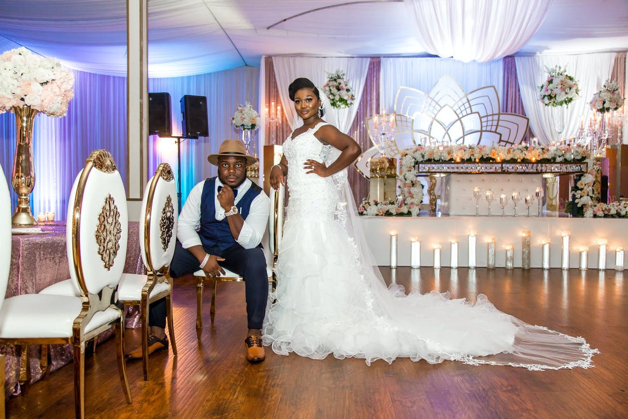Bride Puts Hand on Shoulder of Sitting Groom at Glam, Purple-Up Lit Wedding Reception Planned by Doyin Fash Events   PartySlate