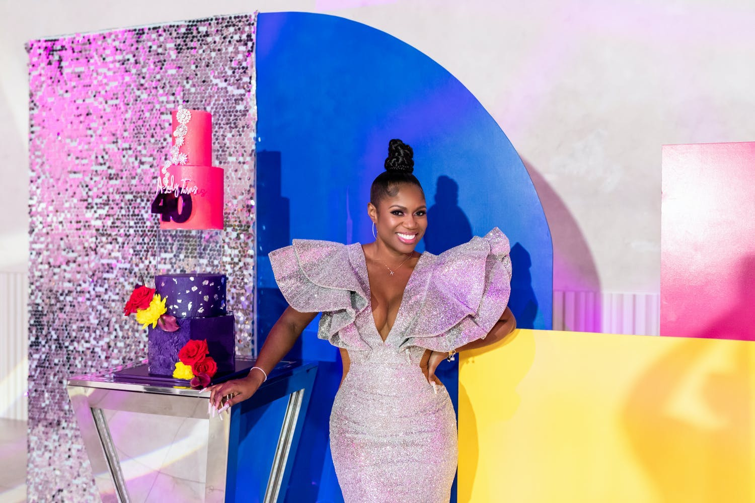 Woman Poses Against Colorful and Glittery Geometric Backdrop for Birthday Party | PartySlate
