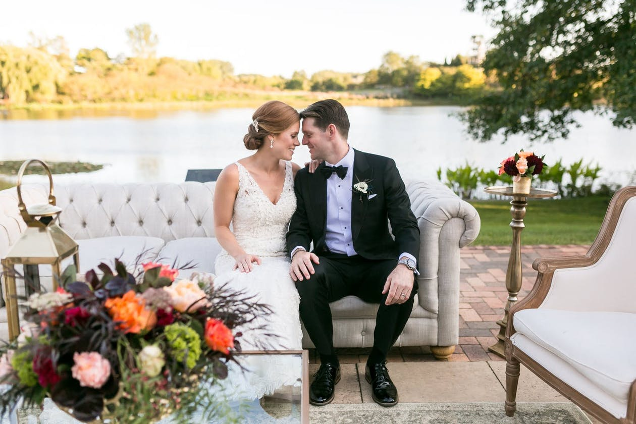 Bride and Groom Sit on White Sofa Against Lake Backdrop at Chicago Botanic Garden in Glencoe, IL | PartySlate
