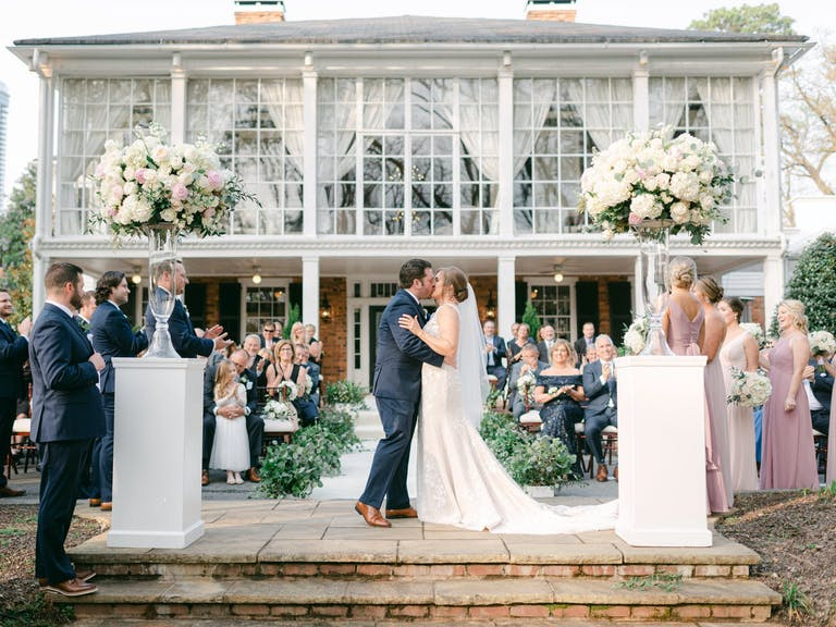 Bride and Groom Kiss at Outdoor Wedding Reception Set Against The Estate by Legendary Events in Atlanta, GA   PartySlate