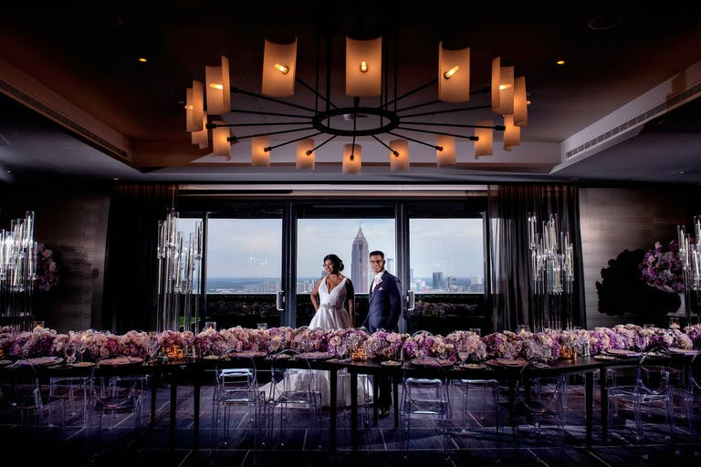 Bride and Groom Stand Between Pink Floral-Lined Tablescape and Windows with City Views at Four Seasons Hotel Atlanta in Atlanta, GA   PartySlate