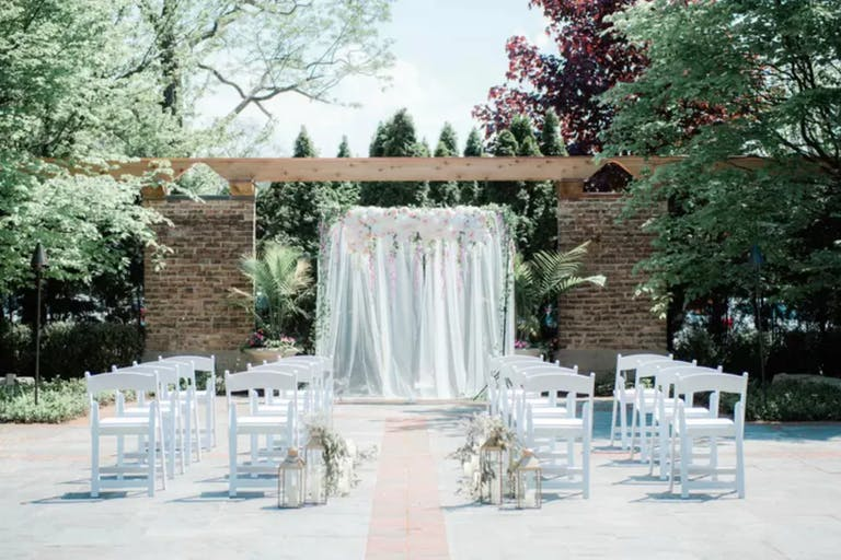 Outdoor all-white wedding ceremony in The Garden Room at Community House Winnetka | PartySlate