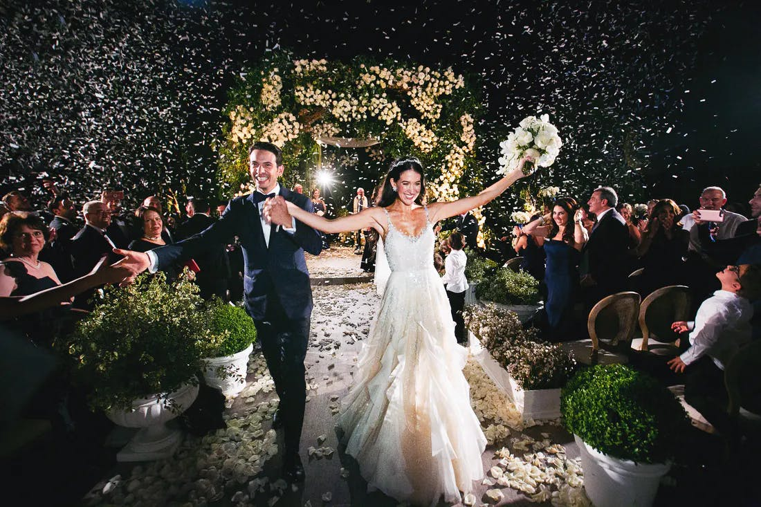 Bride and groom walking down aisle with joy after night wedding ceremony and twinkling lights   PartySlate