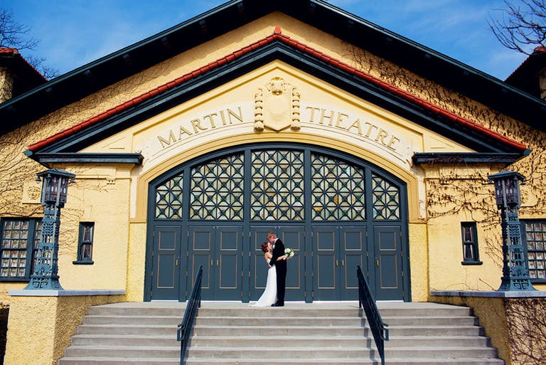 Bride and Groom Embrace Before Blue Doors of Martin Theatre at Ravinia in Highland Park, IL | PartySlate