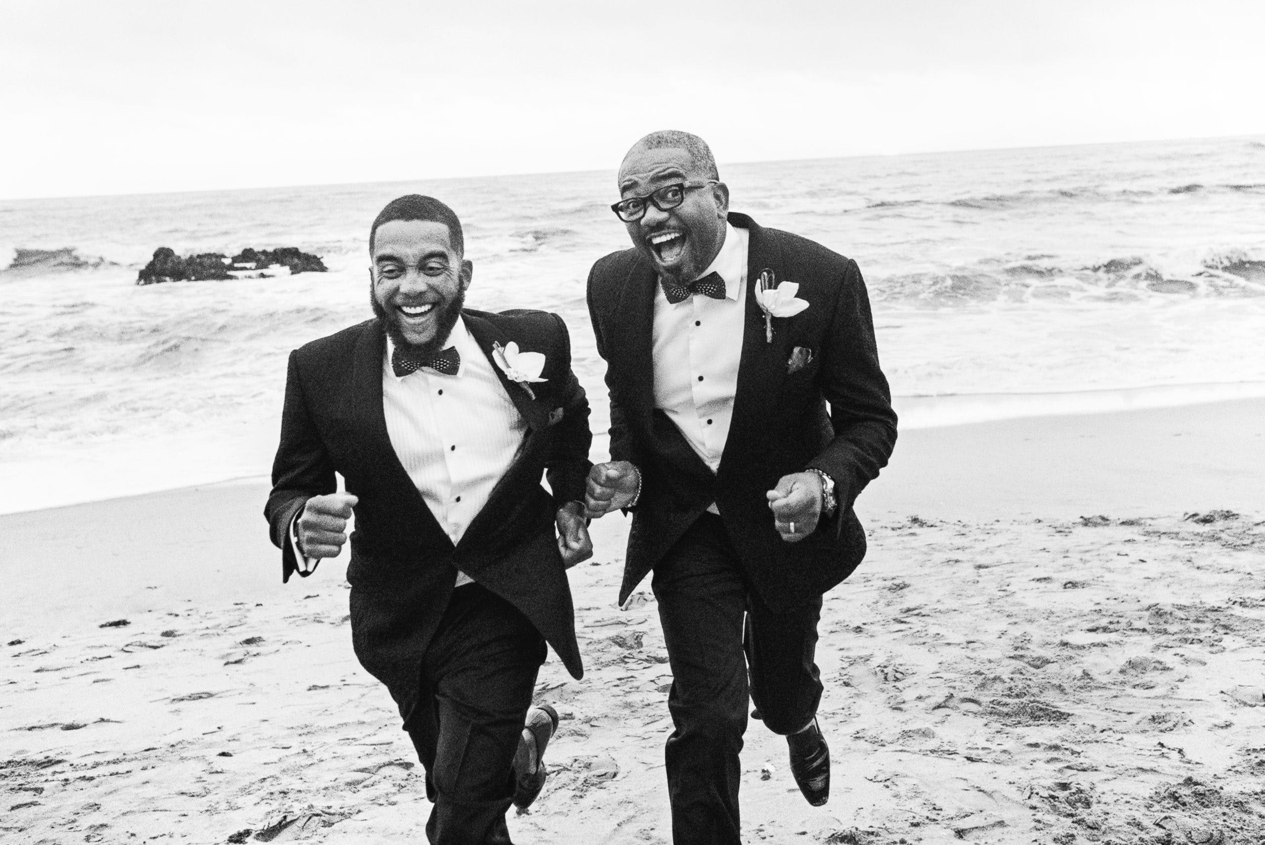 Candid photo of two grooms running on the beach towards camera   PartySlate