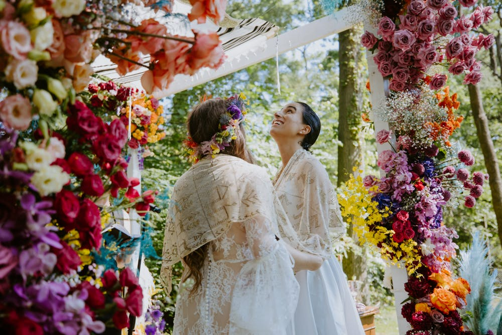 Two brides walking down the aisle at end of ceremony   PartySlate