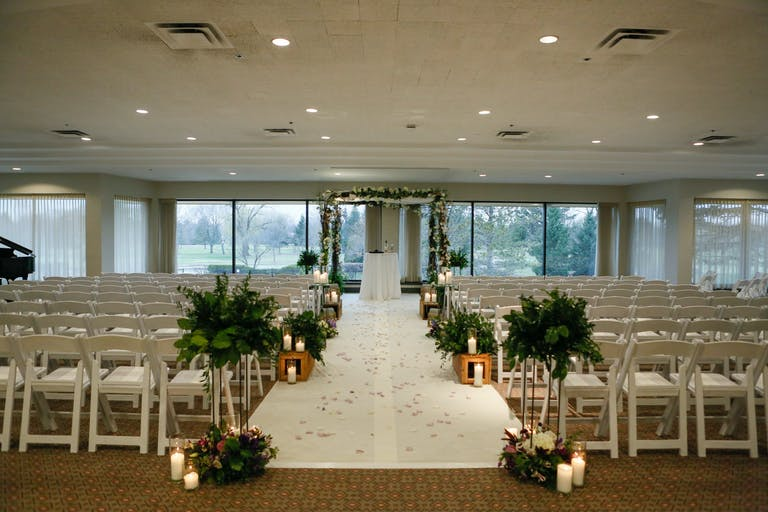 Indoor candlelit ceremony embellished with vines and and white flowers at Ravinia Green Country Club in Riverwoods, IL | PartySlate