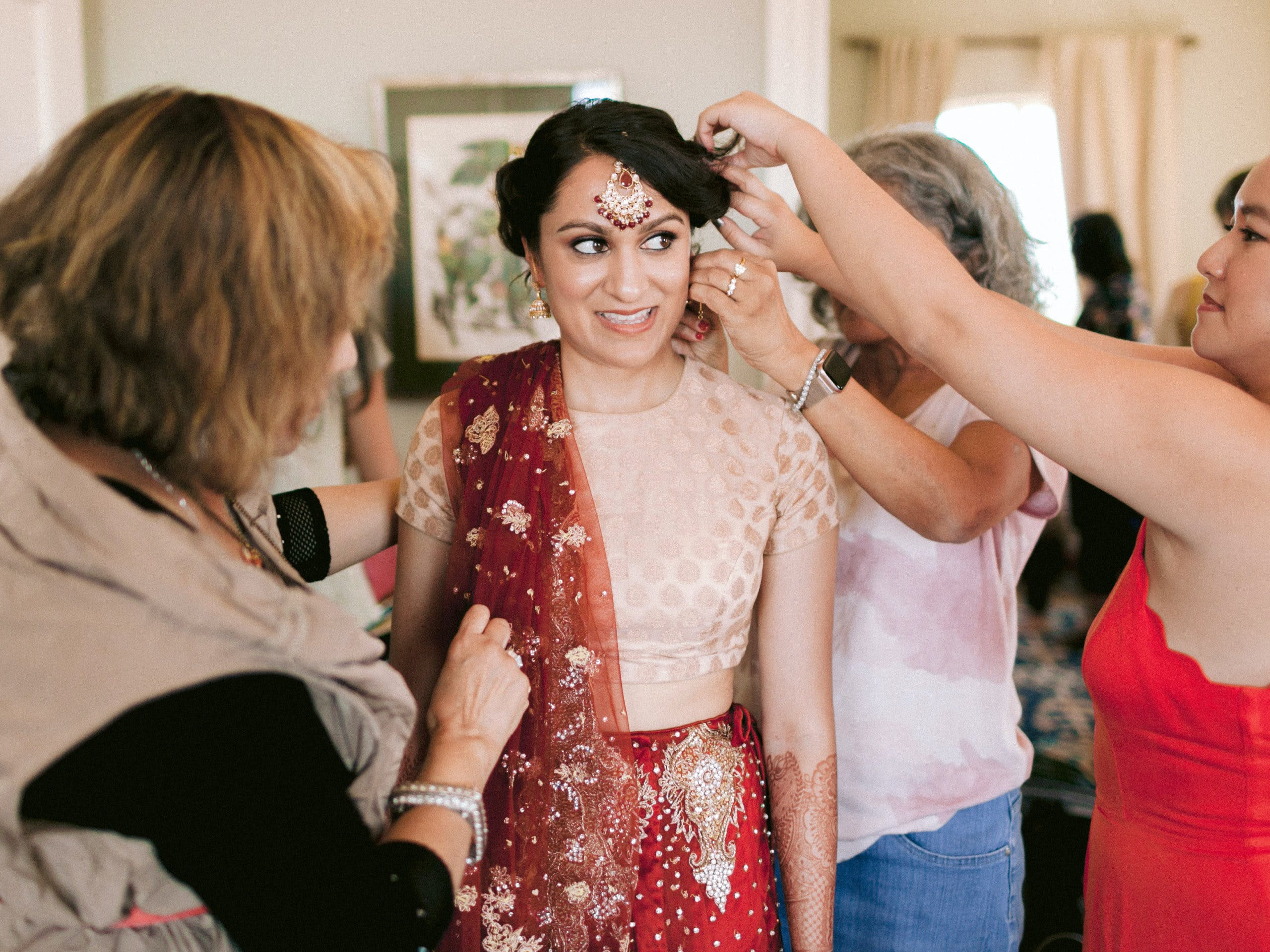 Family helping bride put on earrings and jewelry l PartySlate